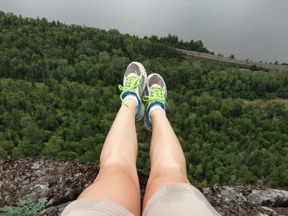 Legs out over the cliff side.
